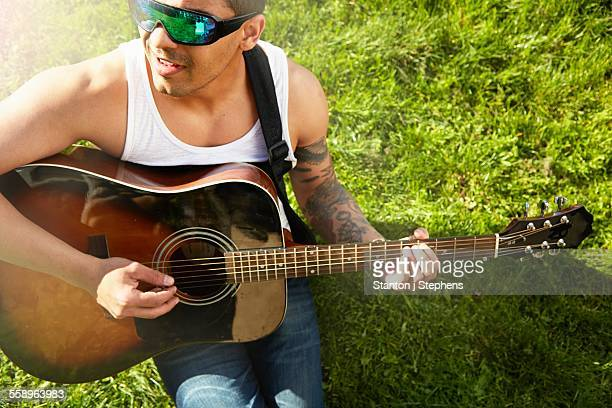 Young man sitting on grass playing acoustic guitar