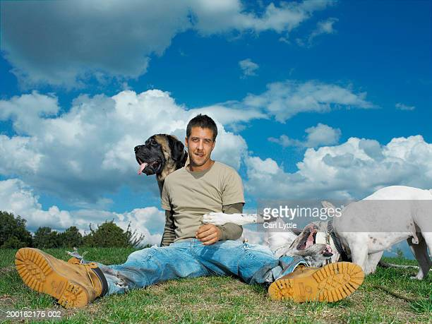 Young man sitting on grass with dogs, portrait
