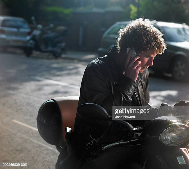 Young man sitting on moped, using mobile phone