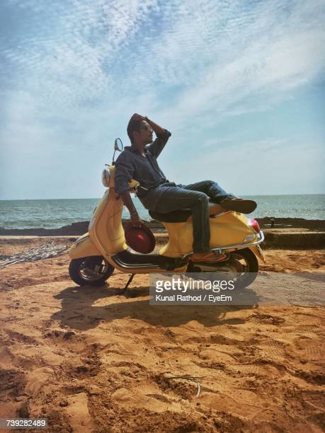 Young Man Sitting On Motor Scooter Parked At Beach Against Sky