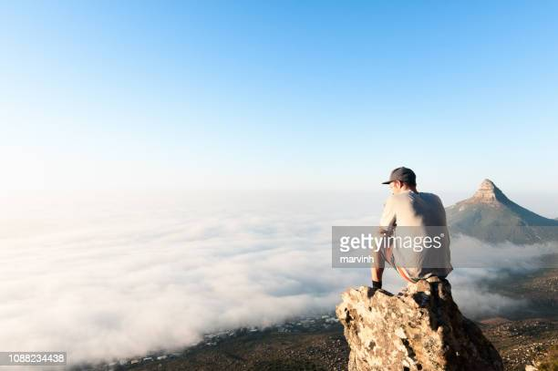 young man sitting on mountain above the clouds of cape town, south africa - top foto e immagini stock