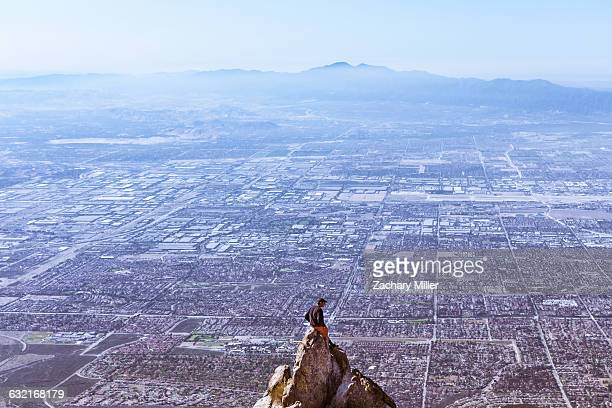young man sitting on mountain top, mount baldy, california, usa - mount baldy stock photos and pictures