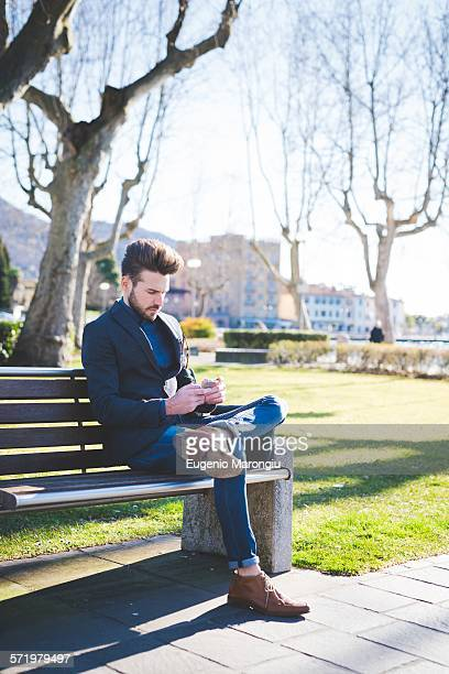 Young man sitting on park bench reading smartphone texts