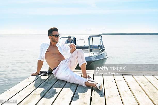Young man sitting on pier, Gavle, Sweden