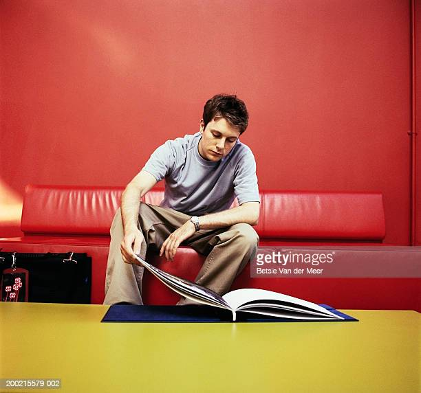 Young man sitting on red sofa looking at book on coffee table
