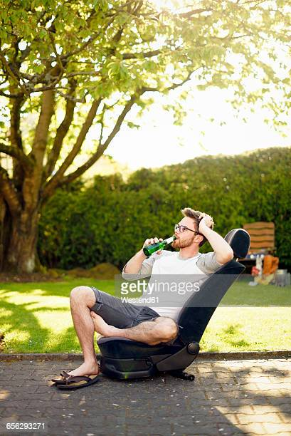 Young man sitting on removed car seat drinking beer