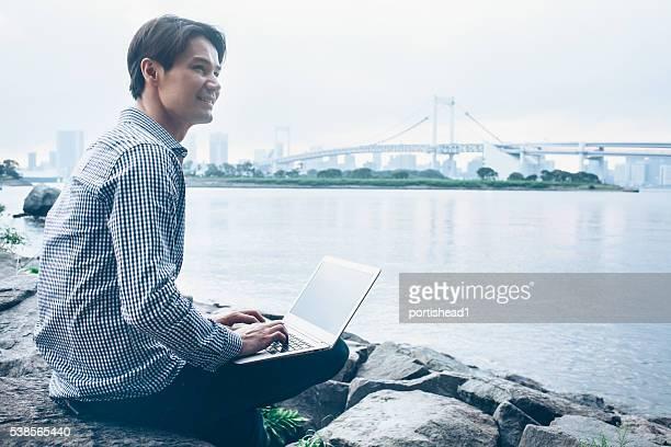 若い男性に座っているリバーサイドとノートパソコンを使う