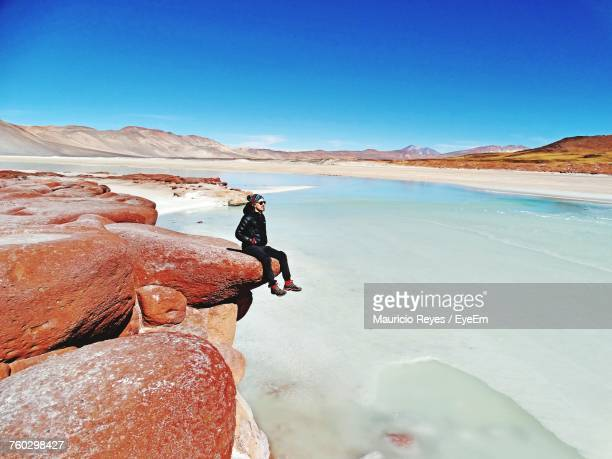 young man sitting on rock against clear blue sky - paisaje espectacular fotografías e imágenes de stock