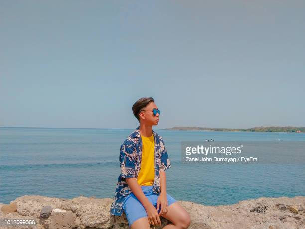Young Man Sitting On Rock At Beach Against Sea And Sky