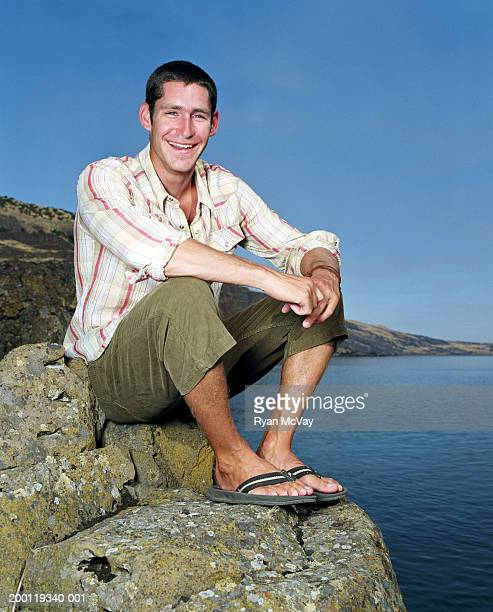 Young man sitting on rock beside river, smiling, portrait