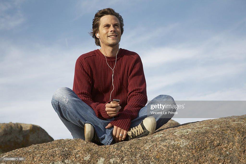 Young man sitting on rock listening to headphones, outdoors : Foto de stock