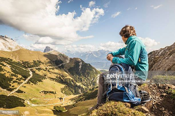 Young man sitting on rock, looking at view, Mount Hochwanner, Wetterstein Mountains, Bavaria