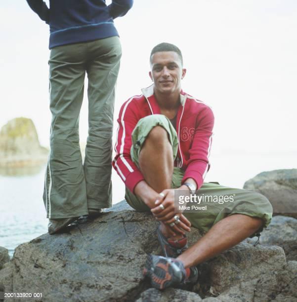 junger mann sitzt auf dem felsen, eine frau an der seite - trainingsoberteil stock-fotos und bilder