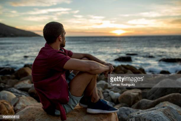 Young man sitting on rocks at the coast at sunset