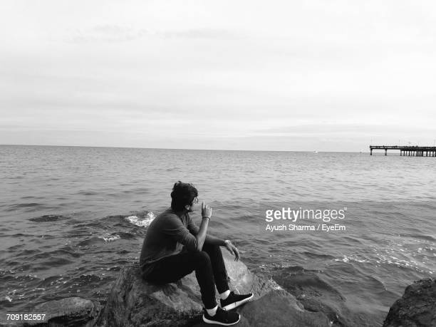 Young Man Sitting On Rocks By Sea Against Clear Sky