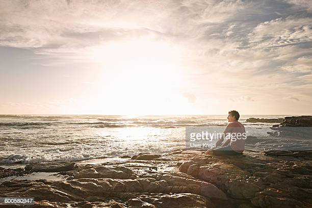 Young man sitting on rocks by the sea