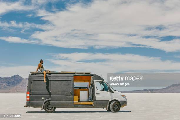 young man sitting on roof of camper van in bonneville salt flats. - western usa stock pictures, royalty-free photos & images
