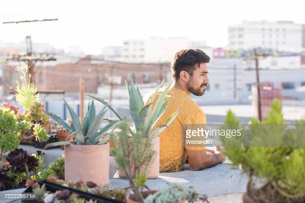 Young man sitting on rooftop terrace