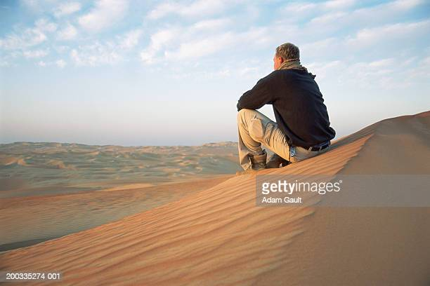 Young man sitting on sand dune in desert landscape