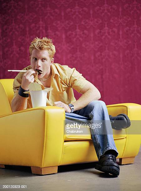 Young man sitting on sofa eating Chinese food out of to-go box