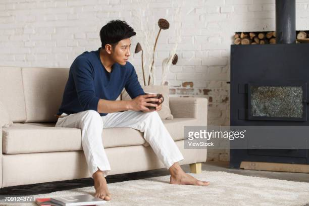 Young man sitting on sofa