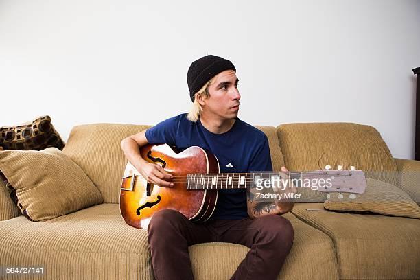Young man sitting on sofa, playing guitar