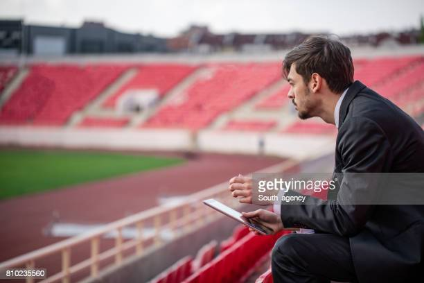 young man sitting on stadium grandstand - sportkleding stock pictures, royalty-free photos & images