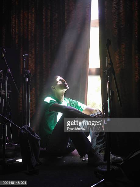 Young man sitting on stage, looking up, sunbeam shining through window