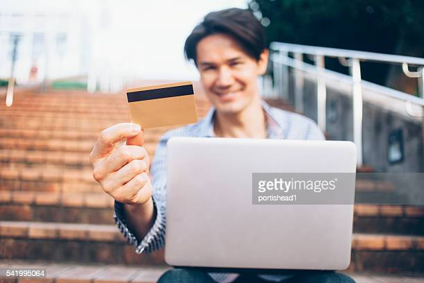 Young man sitting on stairs holding credit card