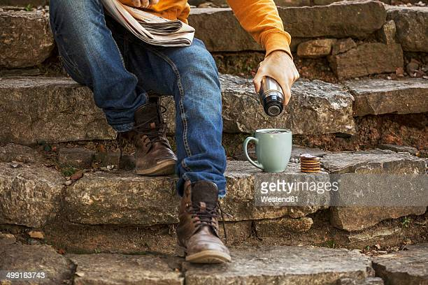 young man sitting on steps having coffee break, partial view - flask stock pictures, royalty-free photos & images