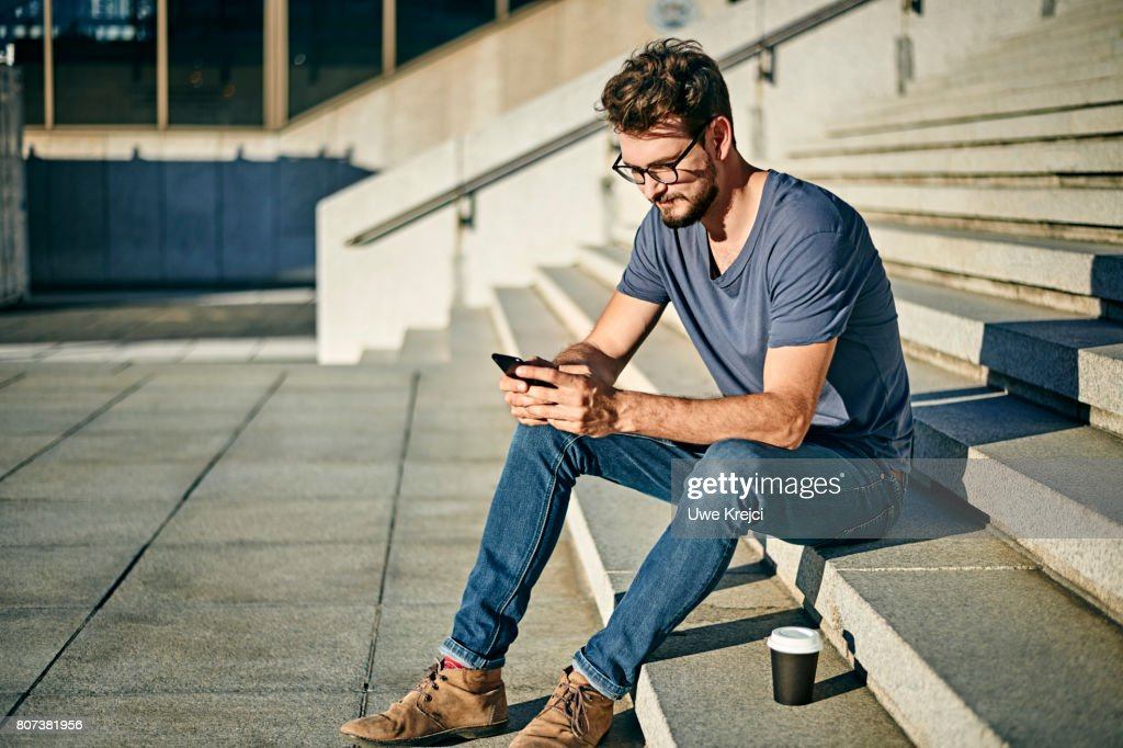 Young man sitting on steps sending text message : Stock Photo