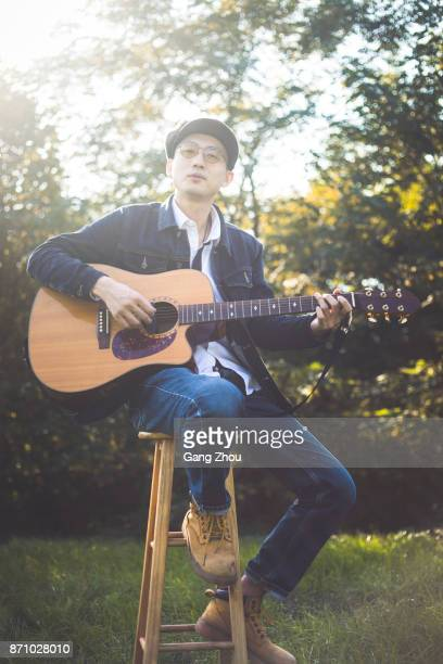 young man sitting on stool playing acoustic guitar on lawn