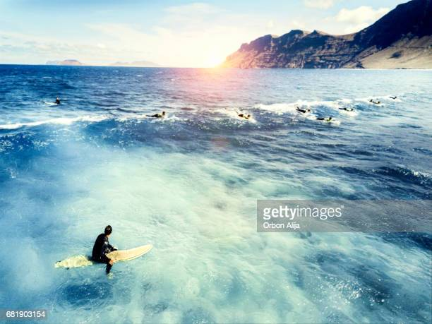 Young man sitting on surf board in sea