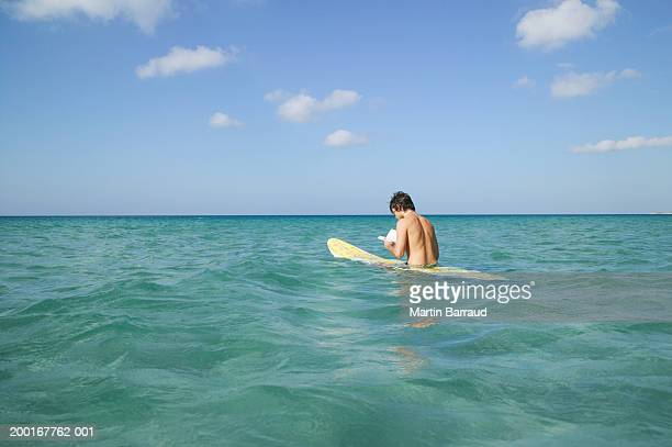 Young man sitting on surfboard in sea, reading book