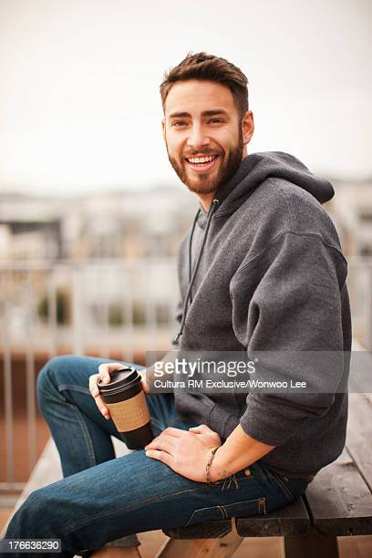 Young man sitting on table holding disposable cup, smiling