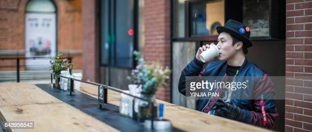 Young man sitting on the bench drinking coffee