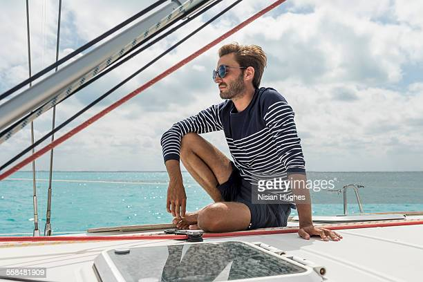 young man sitting on the deck of sailboat