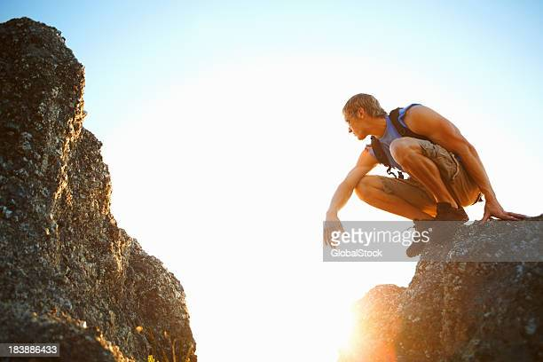 Young man sitting on the edge of a rock
