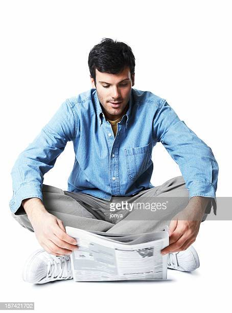 junger mann sitzen auf dem boden lesen zeitung - ganzkörper freisteller editorial stock-fotos und bilder