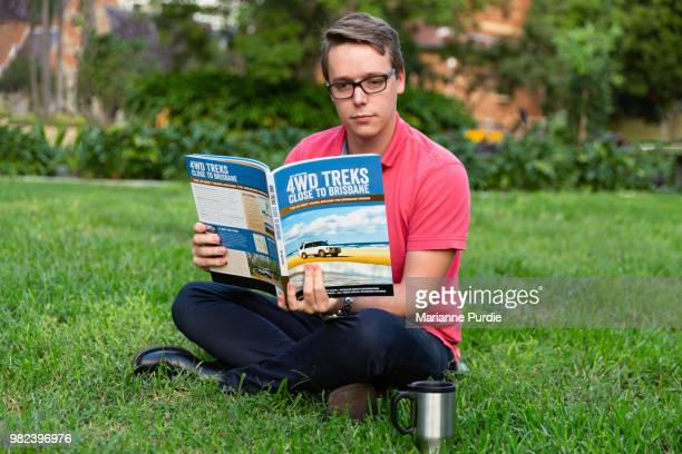 A young man sitting on the grass reading a 4WD trekking book