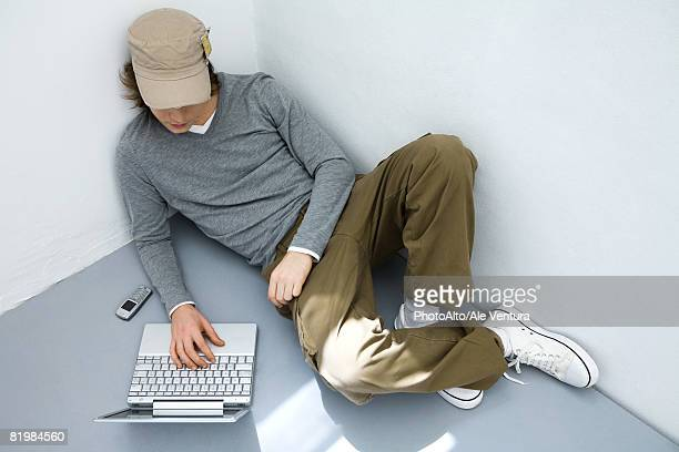young man sitting on the ground, using laptop computer, high angle view - bad posture stock pictures, royalty-free photos & images