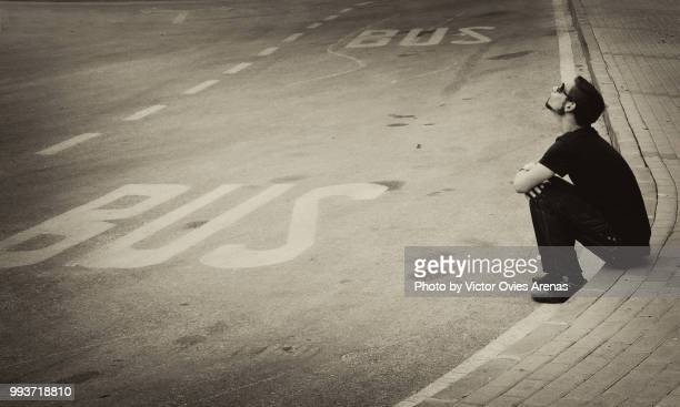 young man sitting on the pavement waiting for the bus - victor ovies fotografías e imágenes de stock
