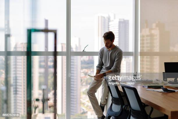 young man sitting on the table with view of the city in the background - brazilian men stock photos and pictures