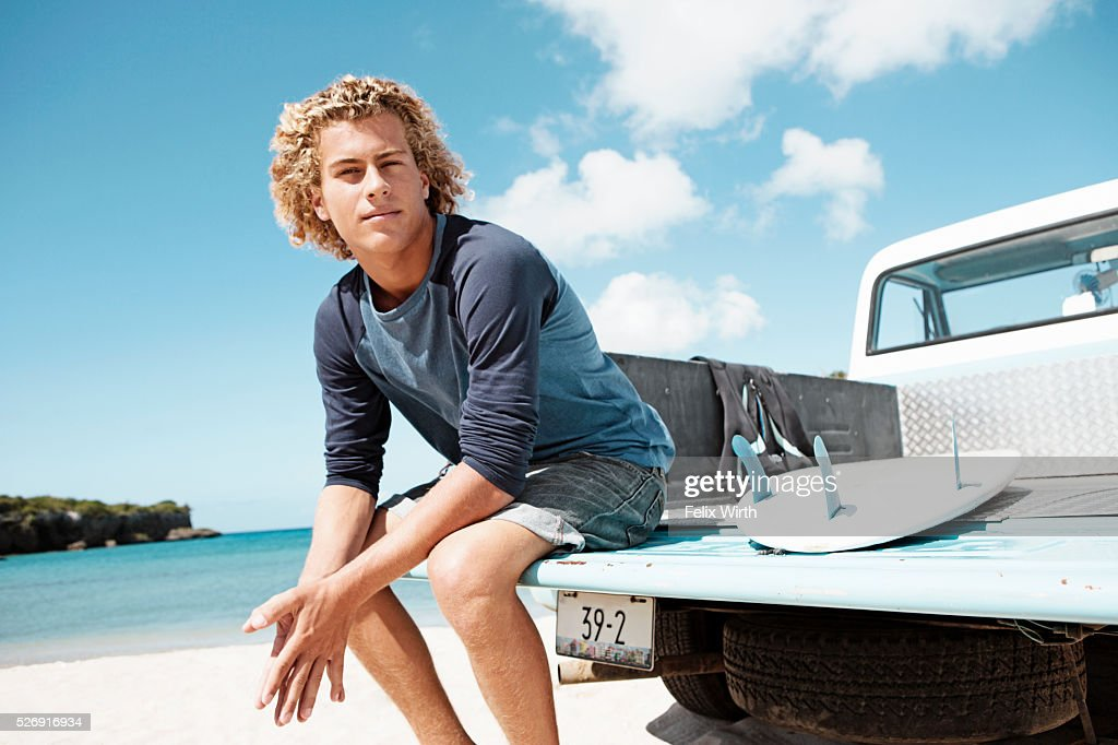 Young man sitting on trailer with surfboard : Stock Photo
