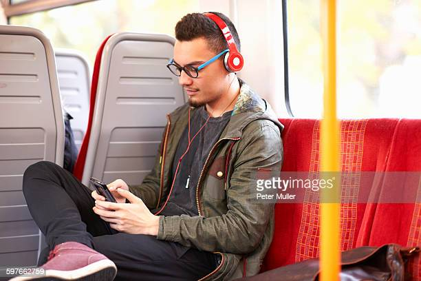 Young man sitting on train, using smartphone, wearing headphones