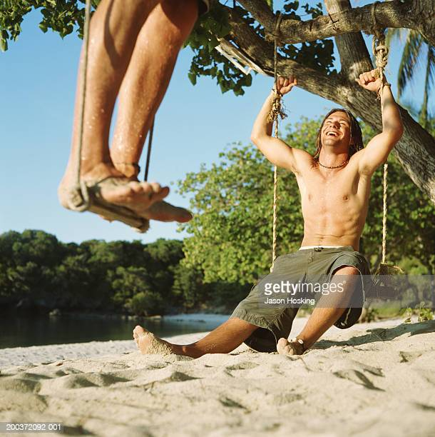Young man sitting on tree swing, laughing