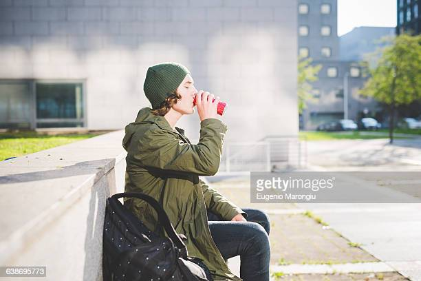 Young man sitting on urban wall drinking from can