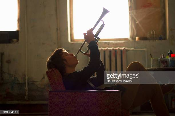 Young man sitting on vintage armchair in artist studio playing trumpet