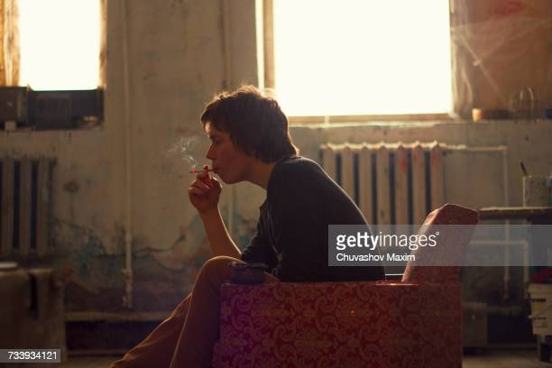 Young man sitting on vintage armchair in artist studio smoking cigarette