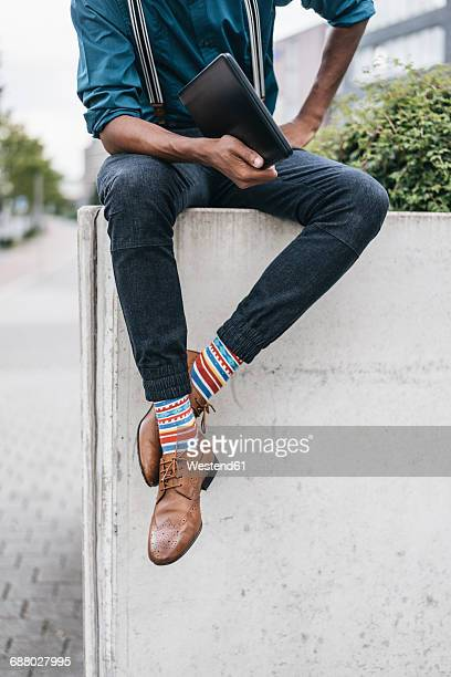 young man sitting on wall, holding laptop - funky stock pictures, royalty-free photos & images